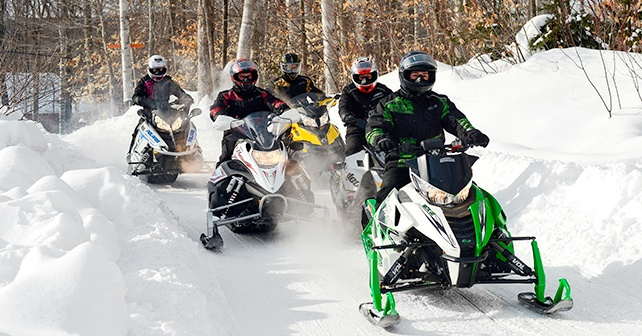 group of snowmobilers trail riding